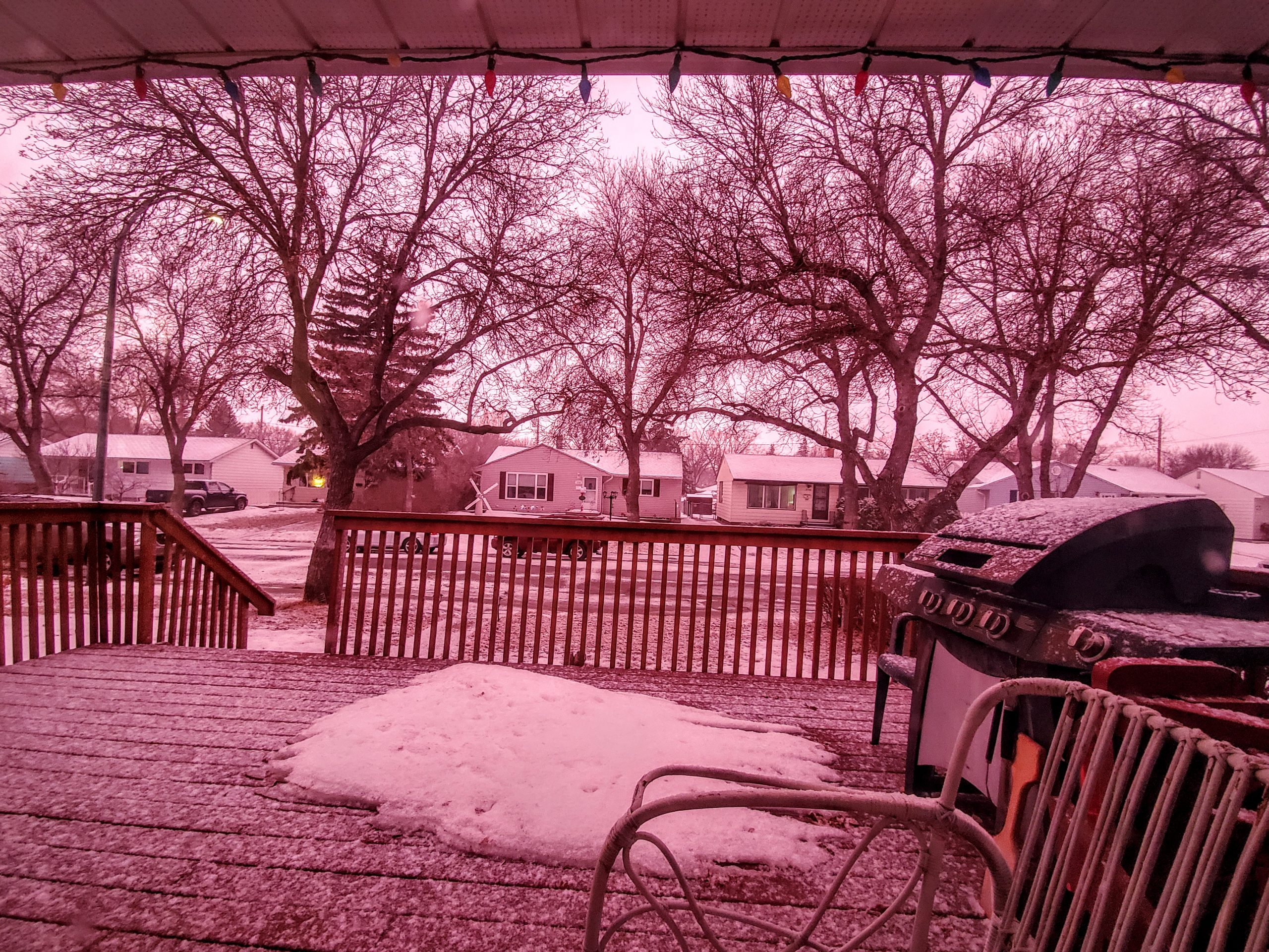 pink hue from sunset during snowfall